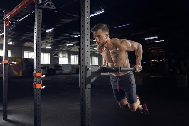 Jovem atleta saudável fazendo exercícios na academia