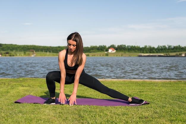 Jovem atlética alongando o tendão da coxa, pernas fazendo exercícios antes do treino na praia do lago