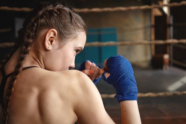 Jovem atlética com duas tranças e costas musculosas, usando bandagens, em posição defensiva