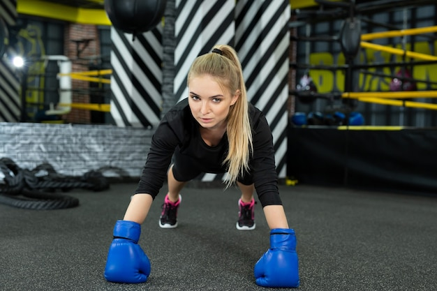 Jovem atlética com luvas de boxe fazendo flexões no ginásio no ringue