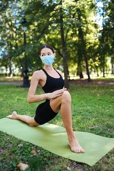 Jovem atlética com uma máscara protetora médica, fazendo ioga no parque pela manhã