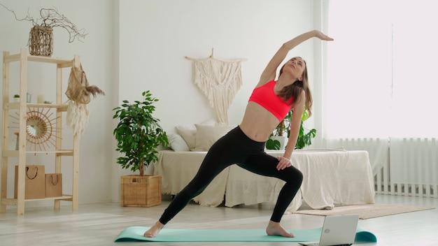 Jovem atlética de legging e top fazendo exercícios de alongamento. mulher pratica esportes em casa
