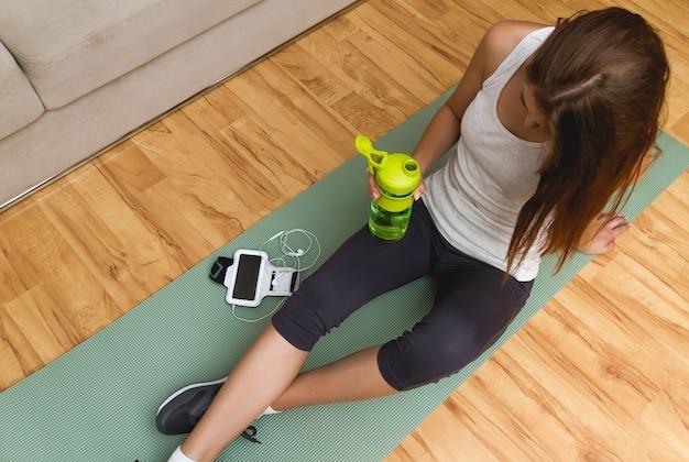 Jovem atlética descansando após exercícios e bebendo água