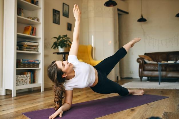 Jovem atlética e enérgica se exercitando dentro de casa, fazendo pose de prancha lateral que ajuda a fortalecer o núcleo, os braços e as pernas.