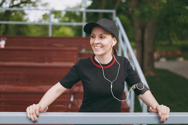 Jovem atlética e sorridente de uniforme preto e boné com fones de ouvido, ouvindo música, descansando e mantendo-se em pé antes ou depois de correr, treinando no parque da cidade ao ar livre
