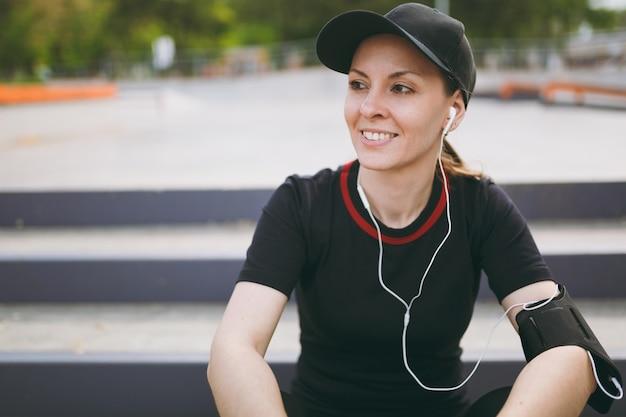 Jovem atlética e sorridente de uniforme preto e boné com fones de ouvido, ouvindo música, descansando e sentado antes ou depois de correr, treinando nas escadas no parque da cidade ao ar livre