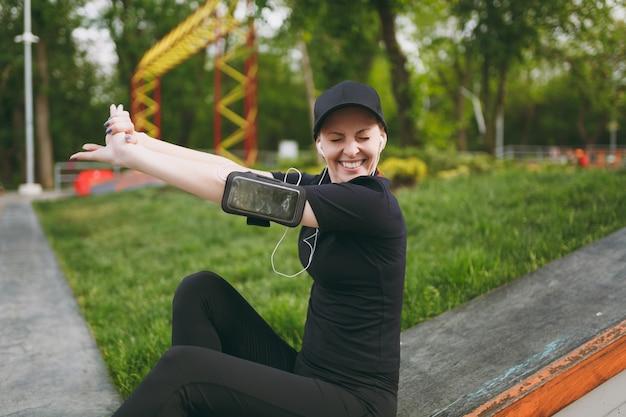 Jovem atlética e sorridente em uniforme preto com fones de ouvido, ouvindo música, esticando as mãos, descansando e sentado antes ou depois de correr, treinando no parque da cidade ao ar livre