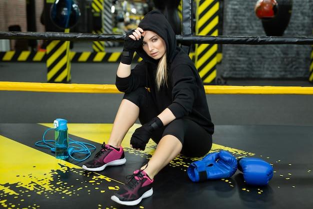 Jovem atlética em um agasalho de treino preto sentada no ringue