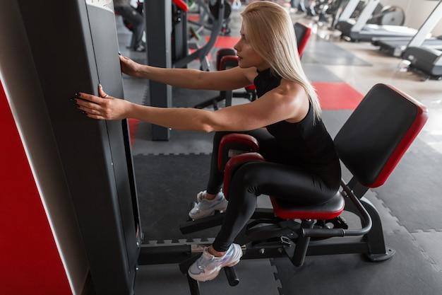 Jovem atlética em um elegante traje esportivo preto com tênis que trabalha em um simulador na academia