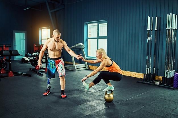 Jovem atlética fazendo exercícios de alongamento no ginásio moderno.