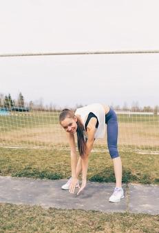 Jovem atlética fazendo exercícios de aquecimento no estádio