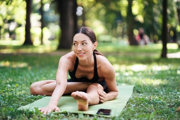 Jovem atlética fazendo ioga no parque pela manhã.