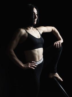 Jovem atlética linda com músculos de uniforme preto, posando para o lado