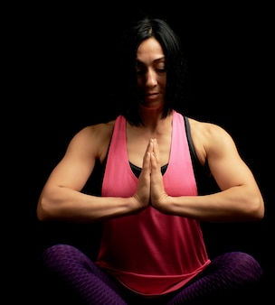 Jovem atlética linda em um top rosa senta-se com as pernas cruzadas em uma posição de lótus