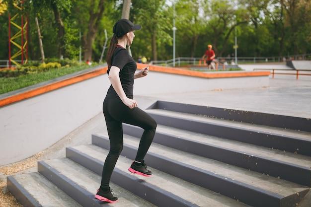 Jovem atlética linda morena de uniforme preto, boné com fones de ouvido, fazendo exercícios de esporte, treinando e correndo, subindo em escadas no parque da cidade ao ar livre