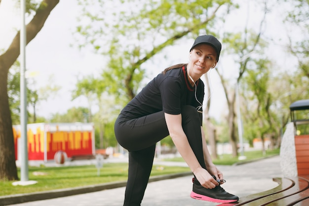 Jovem atlética linda morena de uniforme preto e boné com fones de ouvido, ouvindo música, amarrando o cadarço antes de correr, treinando no banco no parque da cidade ao ar livre