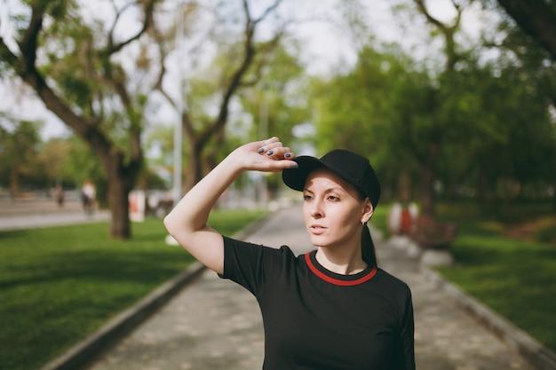 Jovem atlética linda morena de uniforme preto e boné em pé, olhando para o lado, mantendo a mão perto da boné em treinamento em caminho no parque da cidade ao ar livre