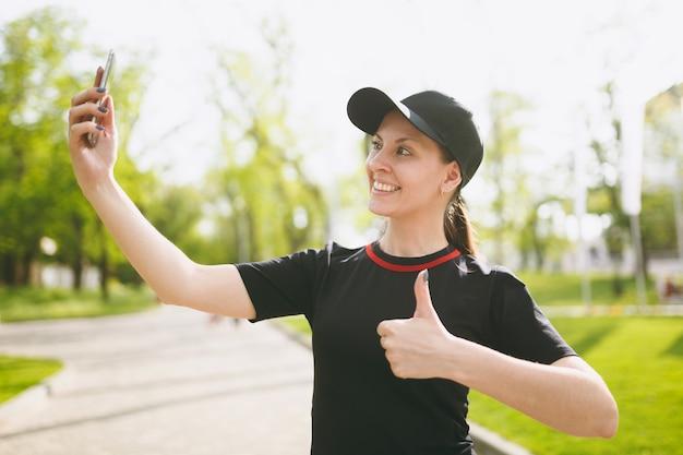 Jovem atlética sorridente linda morena de uniforme preto, boné fazendo selfie no celular durante o treinamento, aparecendo o polegar, parado no parque da cidade ao ar livre