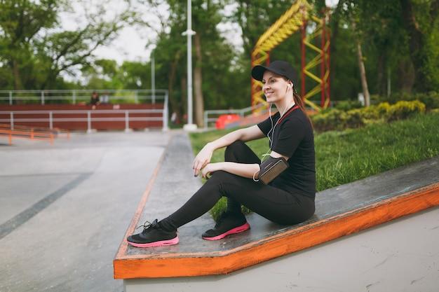 Jovem atlética sorridente linda mulher de uniforme preto e boné com fones de ouvido, ouvindo música, descansando e sentado antes ou depois de correr, treinando no parque da cidade ao ar livre