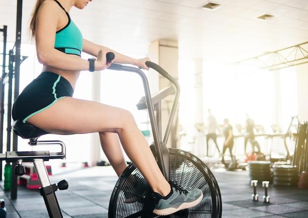 Jovem atlética treina em bicicleta aérea na academia