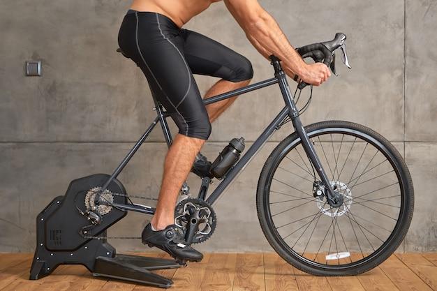 Jovem atlético andando de bicicleta de papelaria em casa