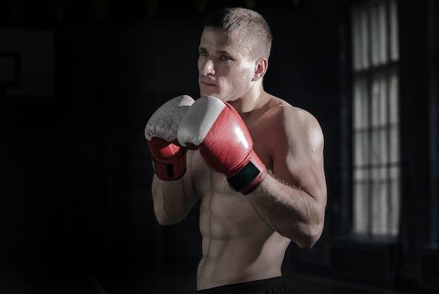 Jovem atlético com luvas de boxe e um rack