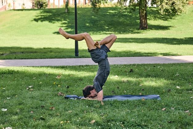 Jovem atlético em roupas esportivas fazendo ioga no parque