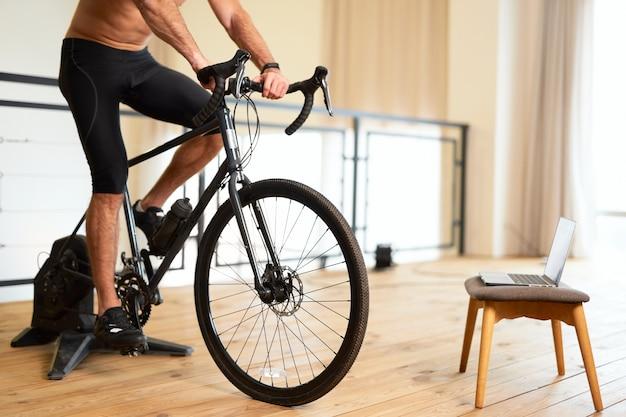 Jovem atlético fazendo exercícios de bicicleta em casa