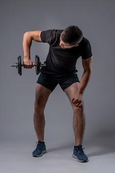 Jovem atlético fazendo exercícios de ombro com halteres