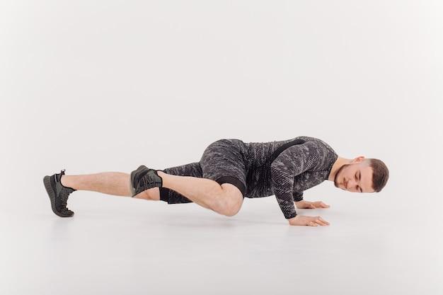 Jovem atlético fazendo exercícios em casa, homem fazendo treinamento, aquecimento antes do exercício de peso.