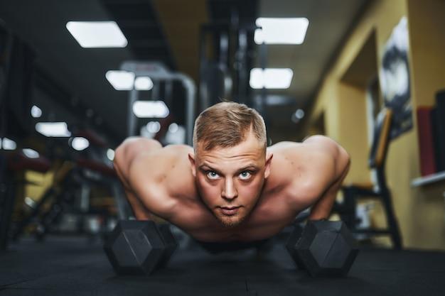 Jovem atlético fazendo flexões na academia e cara forte se exercitando