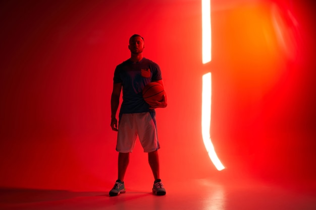 Jovem atlético jogador de basquete segurando uma bola com uma das mãos e luzes traseiras