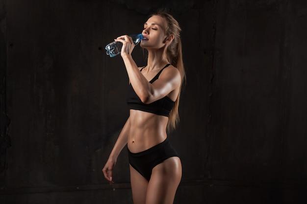 Jovem, atlético, mulher, em, sportswear, bebendo, água