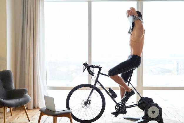 Jovem atlético tirando a camisa enquanto anda de bicicleta dentro de casa em casa