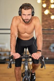 Jovem atlético usando fones de ouvido andando de bicicleta.