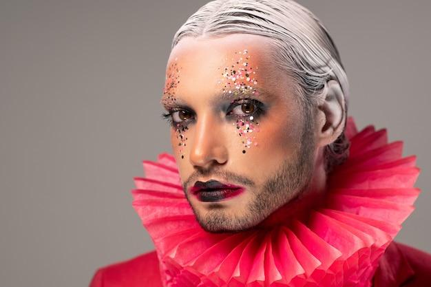 Jovem ator com maquiagem de palco, cabelo branco com penteado preciso e colarinho de bobo da corte de papel vermelho em volta do pescoço olhando para você contra um fundo cinza