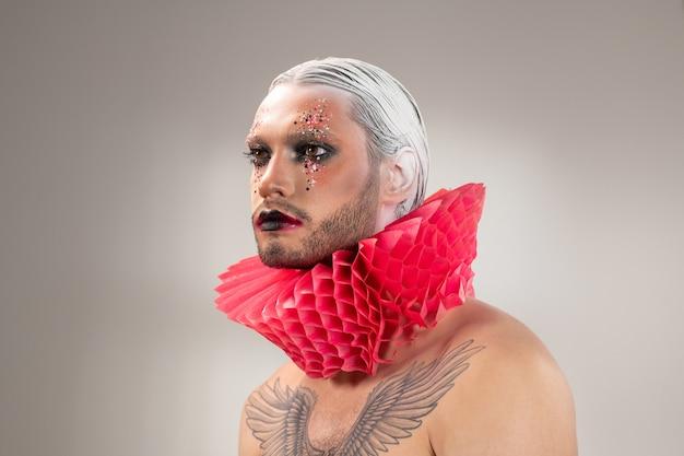 Jovem ator contemporâneo com maquiagem de palco, cabelo branco em penteado preciso e tatuagem no peito usando colarinho de bobo da corte de papel vermelho no pescoço