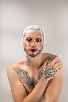 Jovem ator de teatro moderno com maquiagem de palco, cabelos brancos em penteado preciso e tatuagem no peito, pescoço e mão olhando para você isoladamente