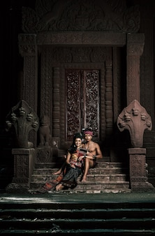 Jovem ator e atriz vestindo lindos trajes antigos, em monumentos antigos, estilo dramático. interprete uma história popular de amor, lenda, um conto popular tailandês chamado