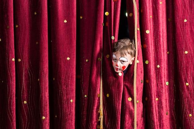 Jovem ator impaciente com pintura facial vermelha colorida espiando por entre as cortinas bordô em um palco, esperando o início da apresentação