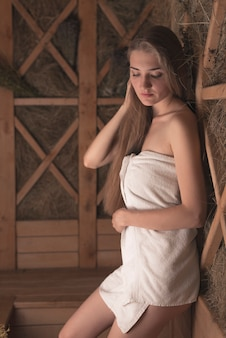 Jovem atraente, apoiando-se na parede de ervas de madeira