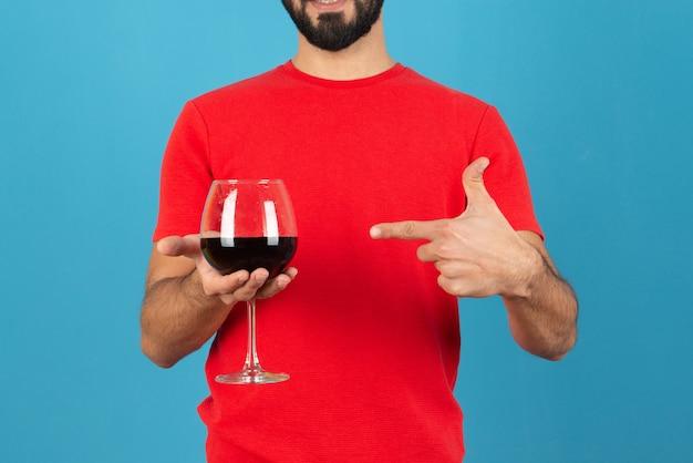Jovem atraente apontando para um copo de vinho tinto.