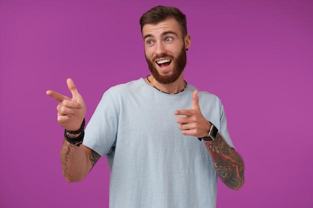 Jovem atraente barbudo alegre com corte de cabelo curto, levantando os dedos indicadores e mostrando-se de lado, feliz, contraindo a testa e sorrindo com a boca aberta, isolado no roxo