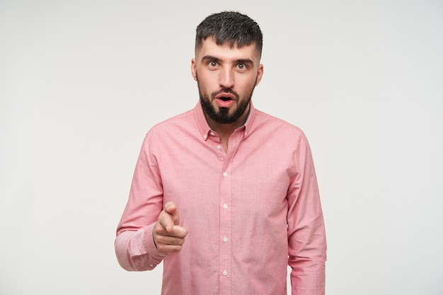 Jovem atraente, barbudo, de cabelos curtos, de olhos abertos, parecendo espantado e levantando o dedo indicador, vestindo roupas casuais em pé sobre uma parede branca