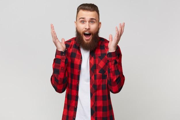 Jovem atraente barbudo de camisa quadriculada não consegue acreditar na sorte que tem, abriu a boca e ergueu a mão de espanto, com penteado fashion bigode, isolado no fundo branco