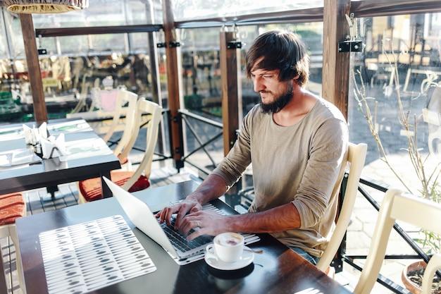 Jovem atraente barbudo digitando no laptop no café ao ar livre