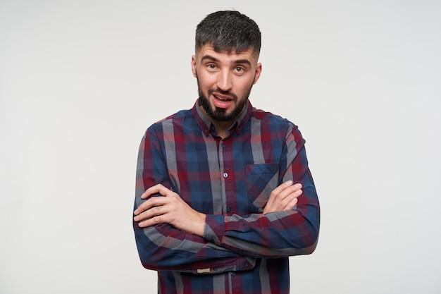 Jovem atraente barbudo e perplexo, com cabelo curto e escuro, mantendo as mãos cruzadas enquanto olha com um rosto perplexo, posando sobre uma parede branca com uma camisa xadrez