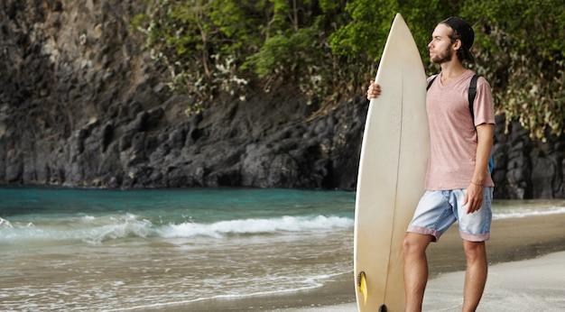 Jovem atraente barbudo em pé com uma prancha de surf em uma praia exótica e olhando para longe