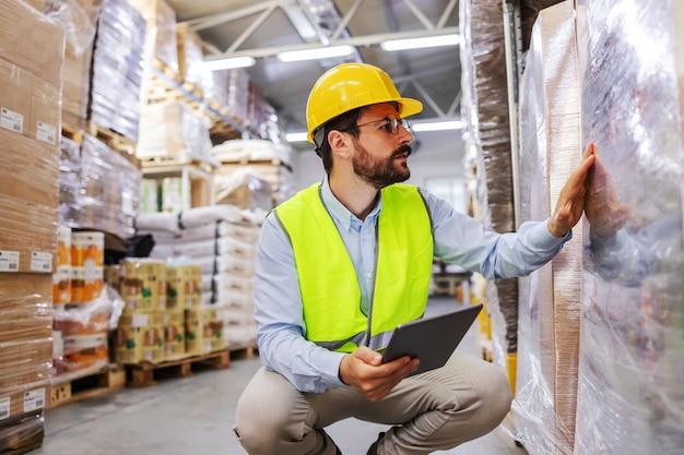 Jovem atraente barbudo empresário no colete e capacete na cabeça, agachado e usando o formulário de tablet, verificando as mercadorias para envio.