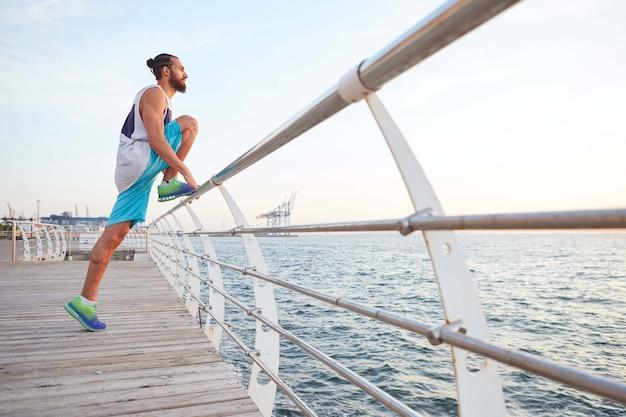 Jovem atraente barbudo esportivo fazendo exercícios matinais à beira-mar, alongamento para as pernas, aquecimento após a corrida.